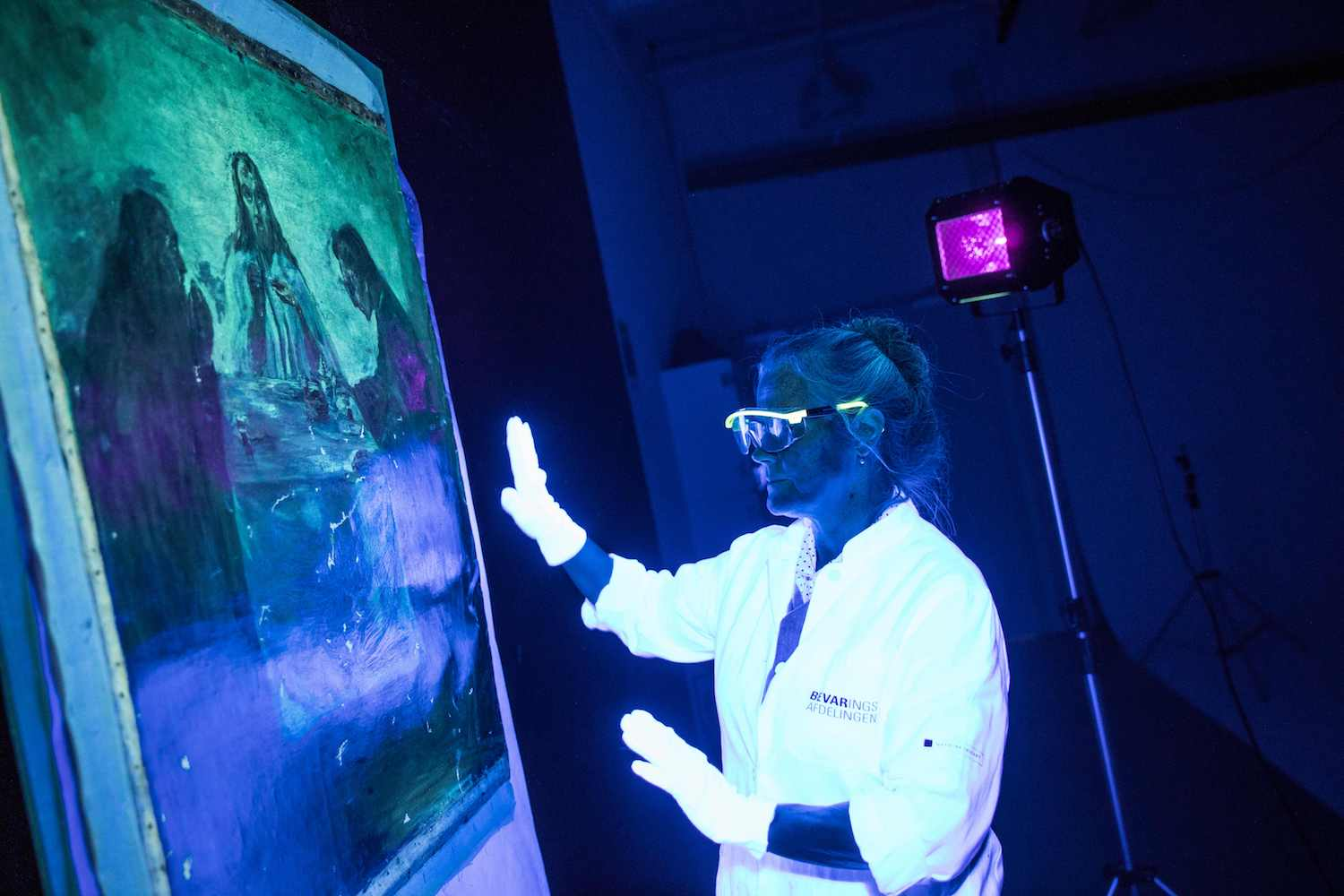 "Taxidermist Mikala Bagge evaluates the damages on the Emil Nolde painting "" Dinner in Emmaus"" with the help of UV lighting at the Danish National Museum in Brede, near Copenhagen, Denmark on February 08, 2018. After having been stolen in 2014 in Oelstrup church close to Ringkoebing in Denmark and emerged in Germany in january 2018 the painting, which has an estimated value of 10 million danish kroner, arrived at the Danish National Museum and will now undergo restoration. / AFP PHOTO / Ritzau Scanpix AND Scanpix / Nikolai Linares / Denmark OUT        (Photo credit should read NIKOLAI LINARES/AFP/Getty Images)"