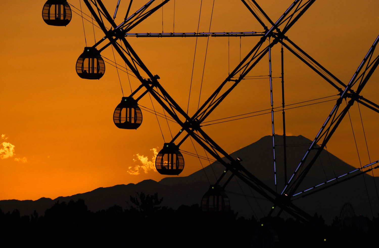 Japan's highest mountain Mt. Fuji is seen in the background over a ferris wheel during sunset at Kasai Rinkai Park in Tokyo on Feb. 6.  (KAZUHIRO NOGI/AFP/Getty Images)