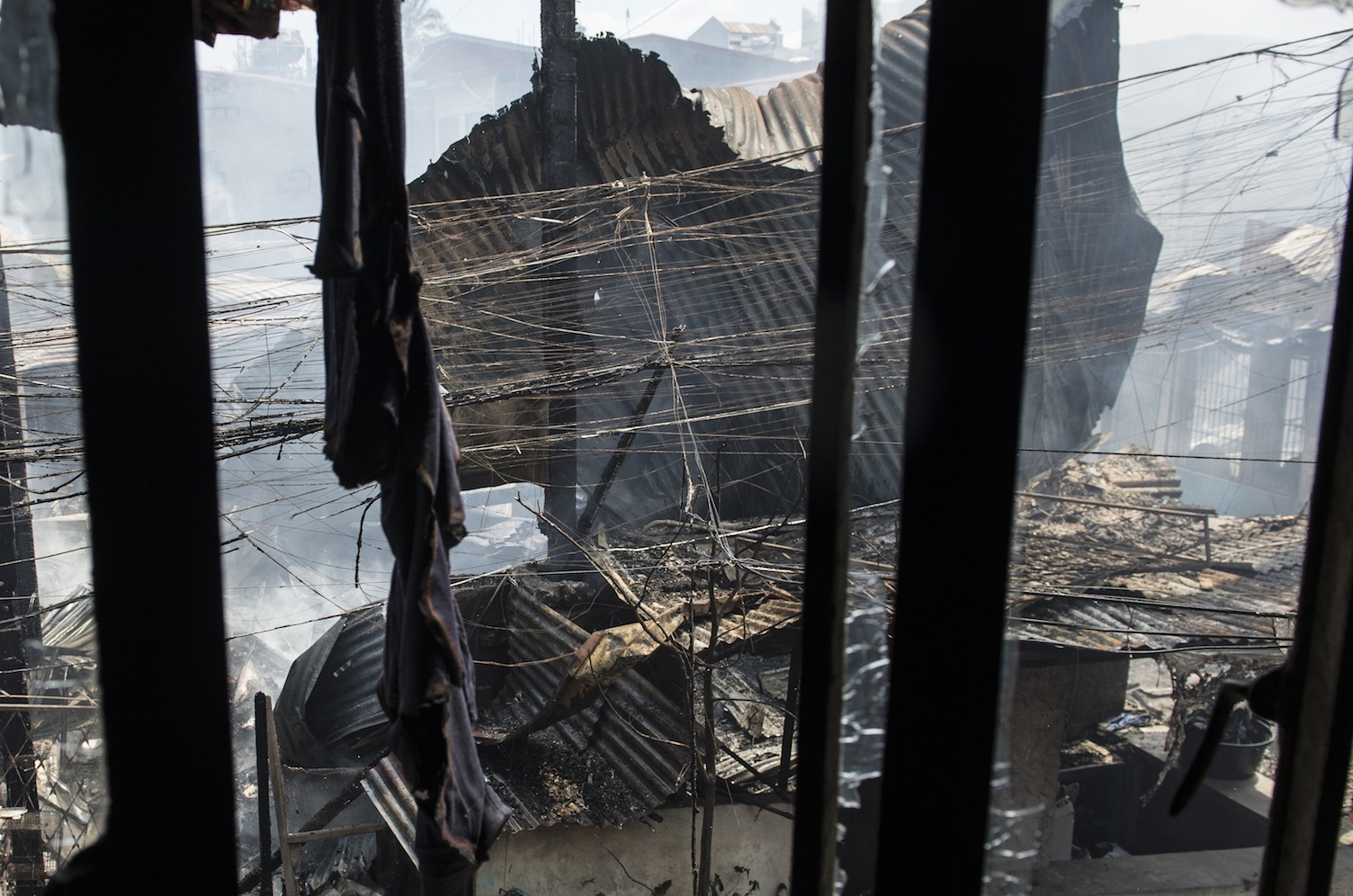 A firefighter (left) sifts through the smoldering rubble of a destroyed house after a fire hit a residential area in Manila on Feb. 23. TED ALJIBE/AFP/Getty Images)