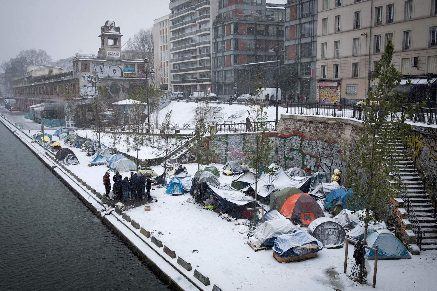 Afghan refugees gather in a makeshift camp as snow falls in Paris on February 9, 2018. The north-west of France has received fresh snowfall, affecting transport in the Ile-de-France region especially in Paris. / AFP PHOTO / JOEL SAGET        (Photo credit should read JOEL SAGET/AFP/Getty Images)