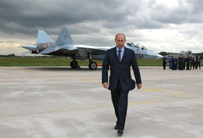 Vladimir Putin walks near a new Russian fighter jet Sukhoi T-50 on June 17, 2010. (ALEXEY DRUZHININ/AFP/Getty Images)