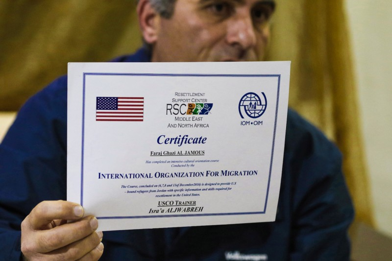 "Faraj Ghazi al-Jamous, a Syrian refugee who was prevented from travel to the United States due to President Donald Trump's executive order blocking entry to citizens from seven Muslim-majority countries, including Syria, holds out a certificate provided by the International Organisation of Migration verifying that he ""completed an intensive cultural orientation course"" for resettlement, in Amman, Jordan, on Feb. 1, 2017. (Khalil Mazraawi/AFP/Getty Images)"