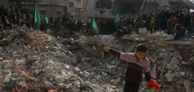 """A Palestinian boy holds a bunch of plastic flowers as he plays on the rubble of assassinated Hamas interior minister Said Siam's apartment building during a Hamas rally in Jabalia, on January 20, 2009. Arab leaders today pledged """"all forms of support for the reconstruction of Gaza"""" but failed to set up a specific fund for the war-battered Palestinian enclave, as they wound up a two-day summit. AFP PHOTO/PATRICK BAZ (Photo credit should read PATRICK BAZ/AFP/Getty Images)"""
