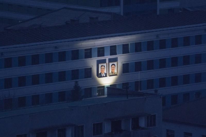 Illuminated portraits of late North Korean leaders Kim Il Sung and Kim Jong Il on display amid the night skyline in Pyongyang, North Korea, on Nov. 25, 2016. (Ed Jones/AFP/Getty Images)