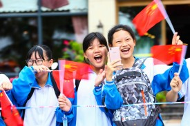 Students watch a street parade in China's southern Hainan province on November 7, 2017. (STR/AFP/Getty Images)