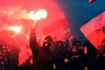 Demonstrators burn flares and wave Polish flags during the annual march to commemorate Poland's National Independence Day in Warsaw on November 11, 2017.