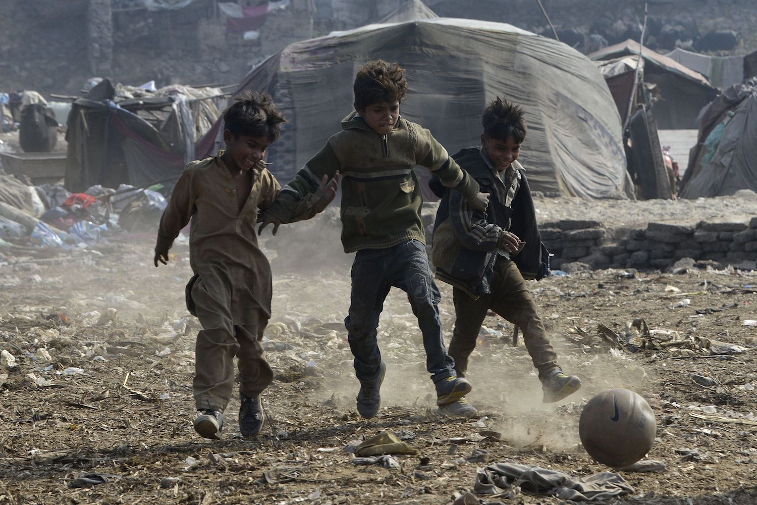 TOPSHOT - Pakistani children play football at a slum in Lahore on January 30, 2018. / AFP PHOTO / ARIF ALI        (Photo credit should read ARIF ALI/AFP/Getty Images)