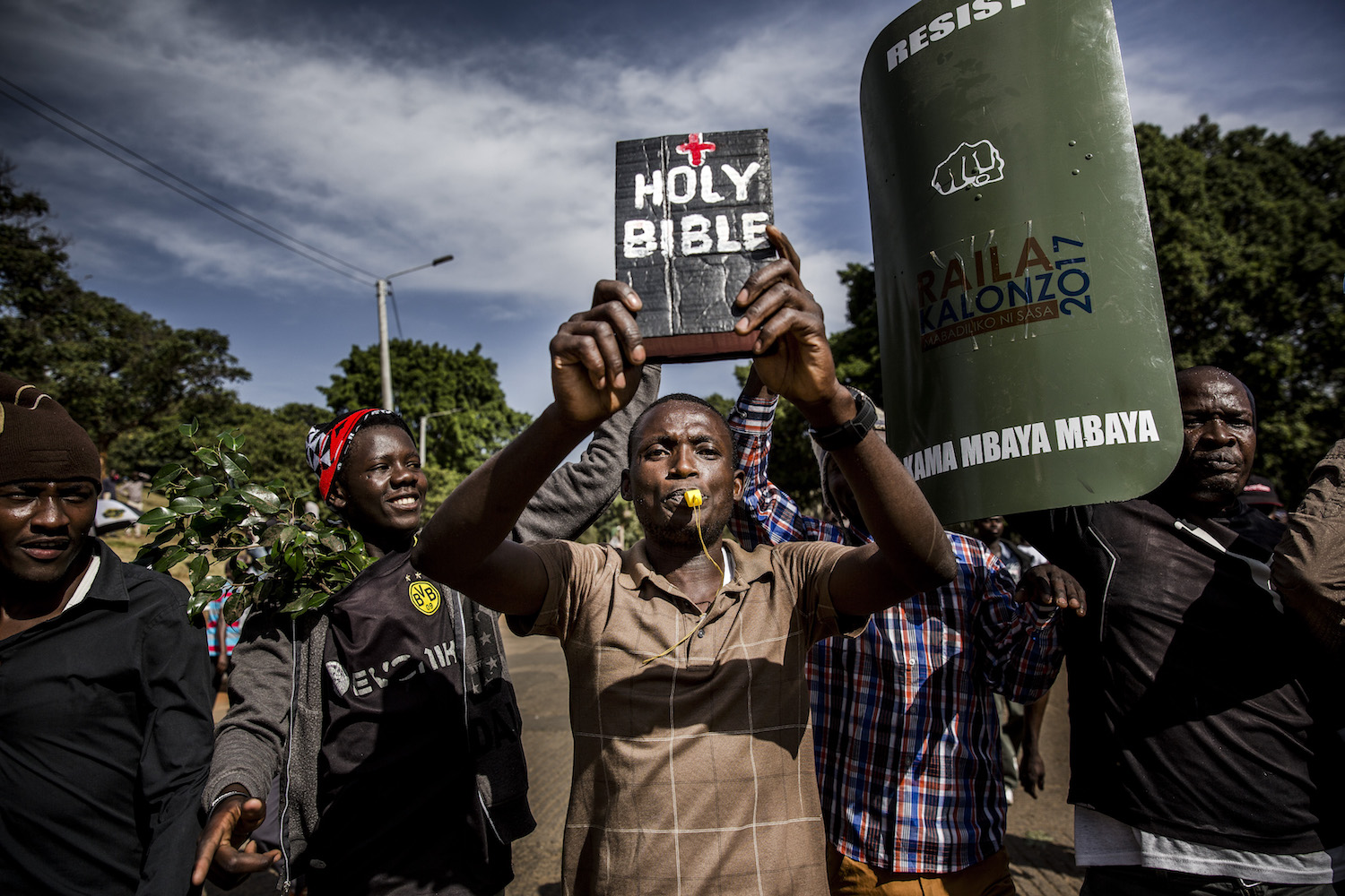 TOPSHOT - A man holds up a bible as supporters of the Kenyan opposition National Super Alliance (NASA) coalition leader react before he has himself sworn in as the 'people's president' on January 30, 2018 in Nairobi. Kenyan opposition leader Raila Odinga had himself sworn in as an alternative president in front of thousands of supporters, three months after an election he claims was stolen from him. / AFP PHOTO / LUIS TATO        (Photo credit should read LUIS TATO/AFP/Getty Images)