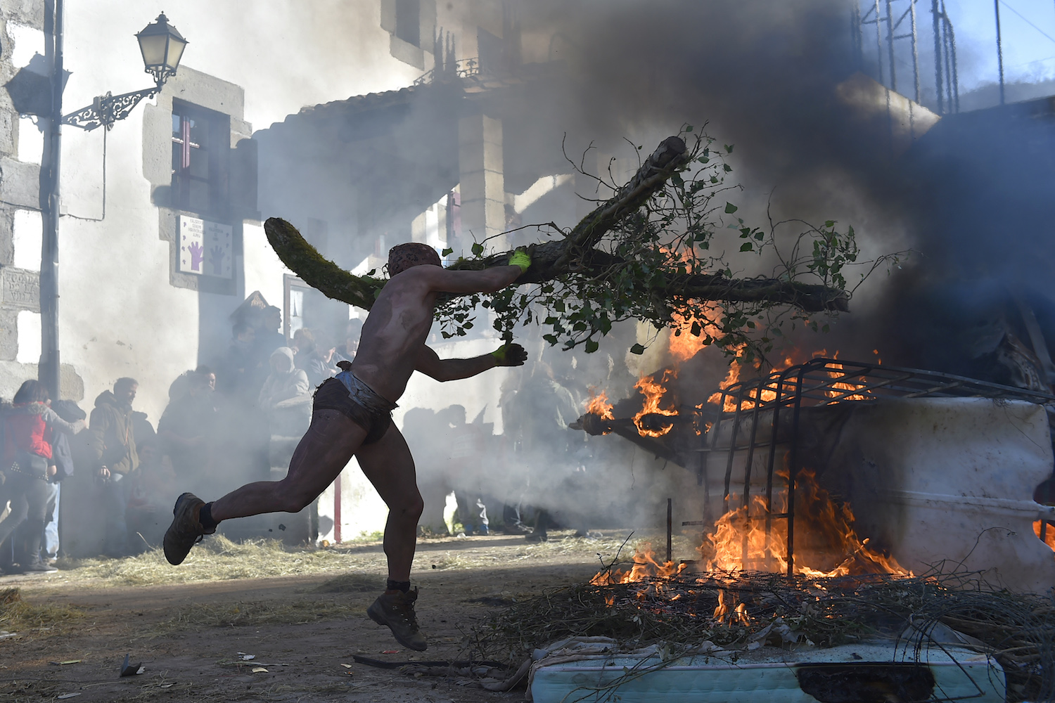 TOPSHOT - A masked participant throws a tree branch to a burning car during the ancient carnival of Zubieta, in the northern Spanish Navarra province on January 30, 2018.  The yearly three day festivities, revolving mainly around agriculture and principally sheep hearding, run on the last Sunday, Monday and Tuesday of January where Navarra Valley locals from two villages dress up and participate in a variety of activites as they perform a pilgrimage through each village. / AFP PHOTO / ANDER GILLENEA        (Photo credit should read ANDER GILLENEA/AFP/Getty Images)