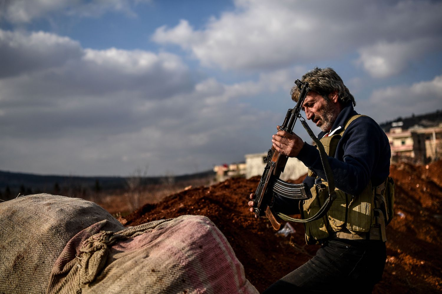 TOPSHOT - A Turkish-backed Syrian rebel fighter stands guard at a checkpoint in the Syrian town of Azaz on a road leading to Afrin, on February 1, 2018. Turkey and allied Syrian rebels have pressed on with Operation Olive Branch in the Kurdish-controlled Afrin enclave despite mounting international concern and reports of rising civilian casualties. / AFP PHOTO / OZAN KOSE        (Photo credit should read OZAN KOSE/AFP/Getty Images)