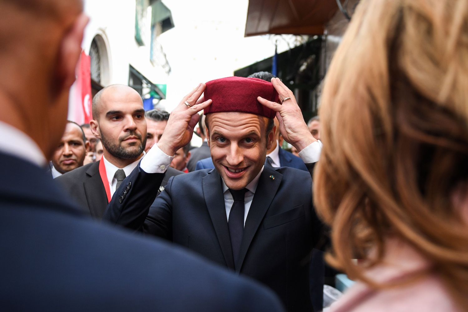 TOPSHOT - French President Emmanuel Macron (C) tries on a fez as he tours the Medina (old town) of the Tunisian capital Tunis on February 1, 2018, during his first state visit to the North African country. / AFP PHOTO / POOL / Eric FEFERBERG        (Photo credit should read ERIC FEFERBERG/AFP/Getty Images)