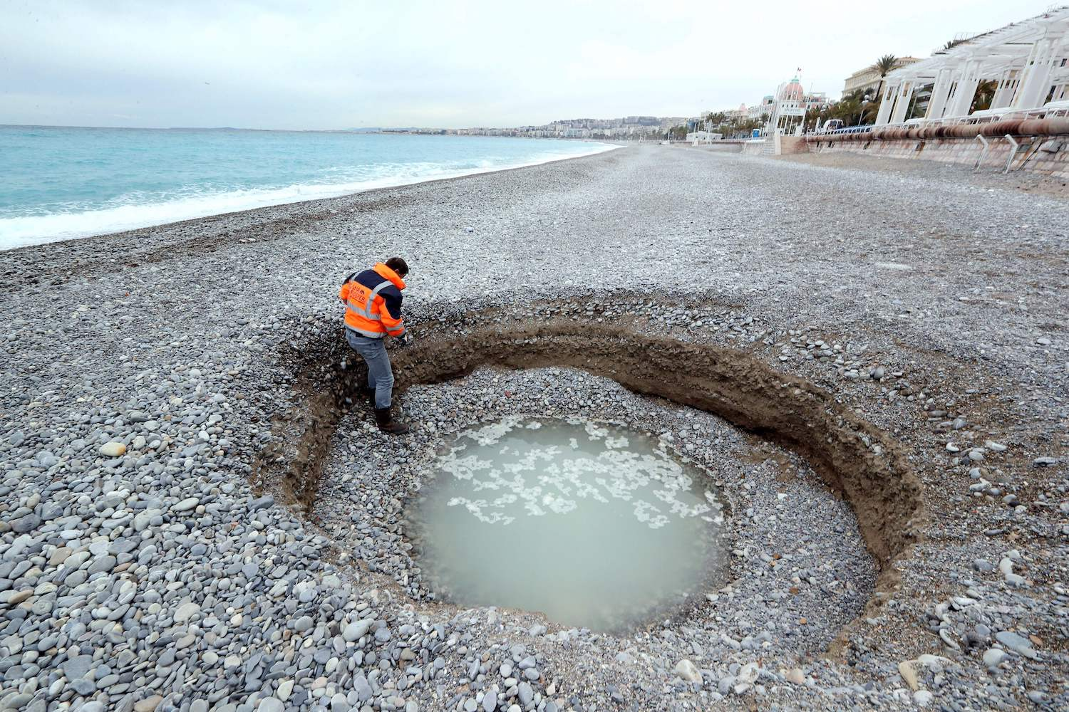 TOPSHOT - People looks at a two-metre deep and five-meter wide crater, filled with brackish water, which has formed on the beach of Lido on the French riviera city of Nice on February 1, 2018.  / AFP PHOTO / VALERY HACHE        (Photo credit should read VALERY HACHE/AFP/Getty Images)