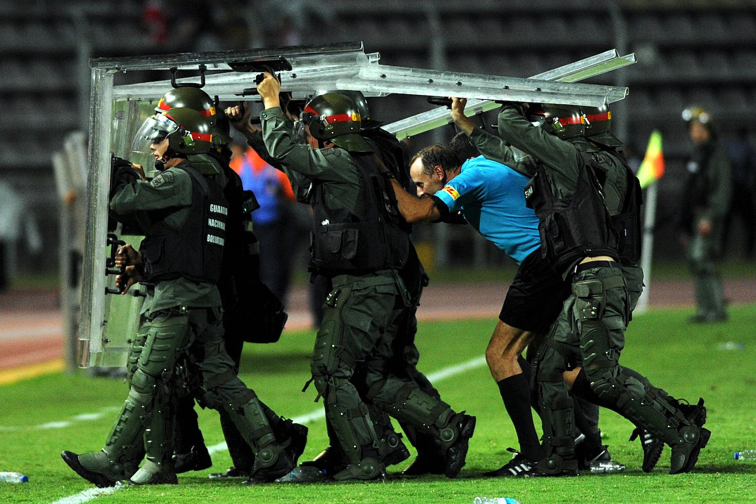 TOPSHOT - Members of the national guard escort Uruguayan referee Daniel Fedorczuk as he leaves the field during a Copa Libertadores football match between Colombian Santa Fe and Venezuela's Tachira at the Polideportivo de Pueblo Nuevo stadium in San Cristobal, Venezuela on February 1, 2018. Venezuelan Tachira supporters disapproved Fedorczuk performance during the match and hurled objects onto the pitch.  / AFP PHOTO / GEORGE CASTELLANOS        (Photo credit should read GEORGE CASTELLANOS/AFP/Getty Images)