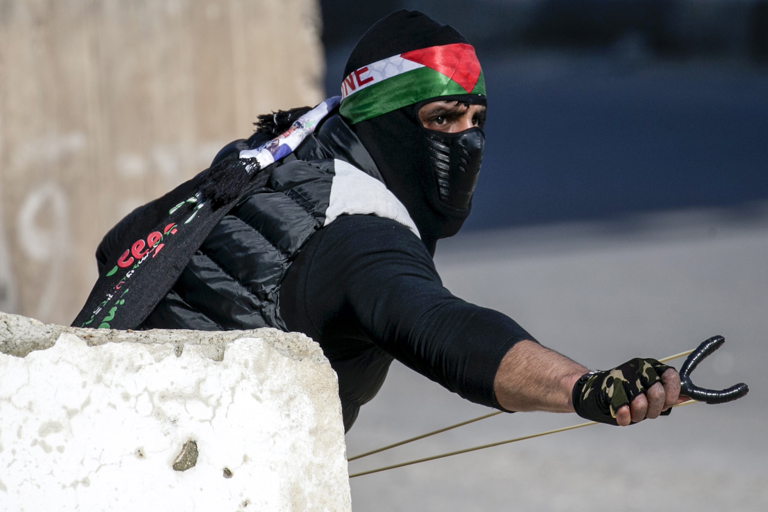 TOPSHOT - A Palestinian protester aims a slingshot during clashes with Israeli soldiers following a demonstration near the Hawara checkpoint, south of the West Bank city of Nablus on February 2, 2018.  / AFP PHOTO / JAAFAR ASHTIYEH        (Photo credit should read JAAFAR ASHTIYEH/AFP/Getty Images)