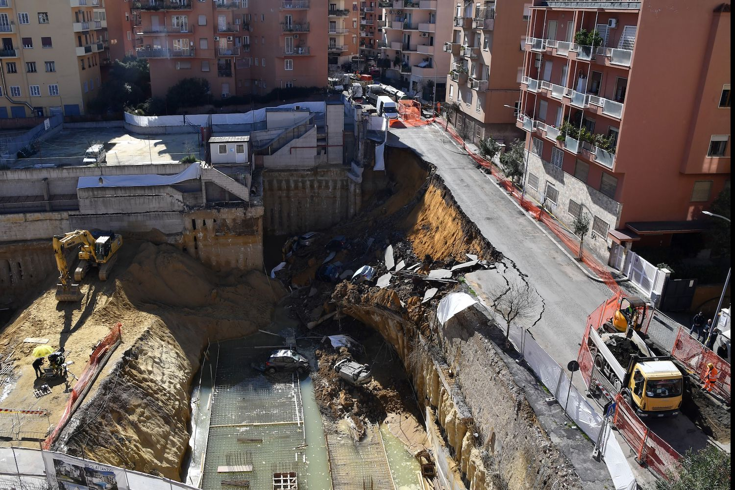TOPSHOT - The picture taken on February 15, 2018 in the street of Balduina's district in Rome shows a general view of a huge sinkhole that opened up the day before in Rome, swallowing six cars. No casualties were reported. About 22 families were evacuated by firefighters following the collapse. The cause of the sinkhole is still under investigation.  / AFP PHOTO / TIZIANA FABI        (Photo credit should read TIZIANA FABI/AFP/Getty Images)
