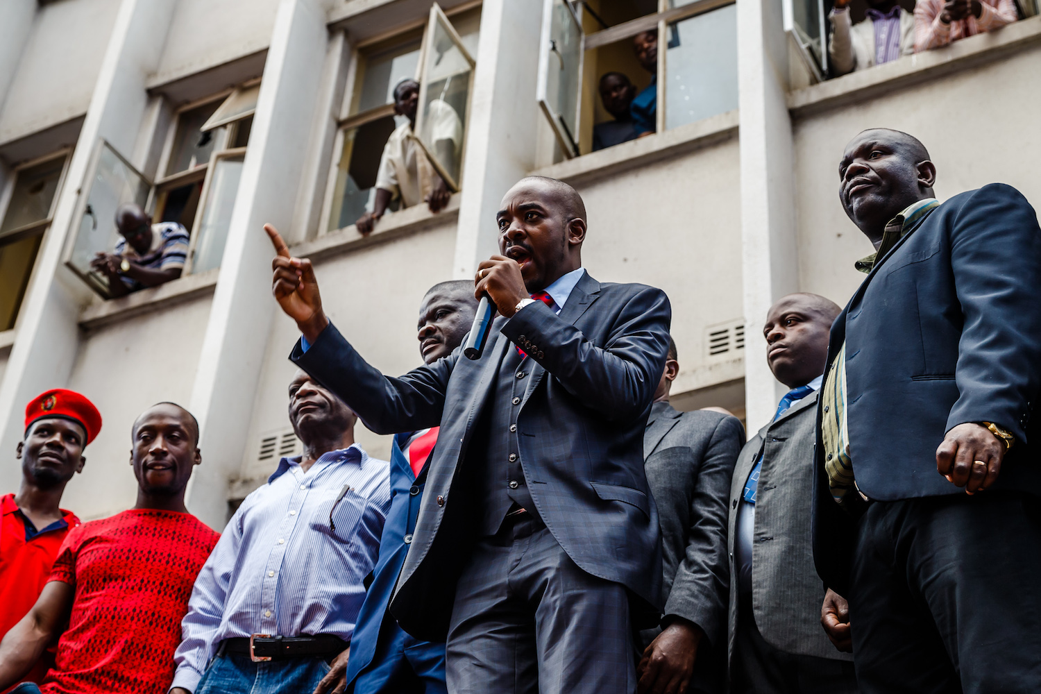 TOPSHOT - Zimbabwe opposition party Movement for Democratic Change (MDC) acting President Nelson Chamisa (C) addresses the crowd gathered outside Harvest House, the party headquarters, in Harare February 15, 2018 following the death of the veteran opposition leader. Zimbabwe was plunged into grief on February 15 following the death of veteran opposition leader Morgan Tsvangirai, roundly praised as a hero, champion of democracy and symbol of resistance who will be hard to replace. / AFP PHOTO / Jekesai NJIKIZANA        (Photo credit should read JEKESAI NJIKIZANA/AFP/Getty Images)