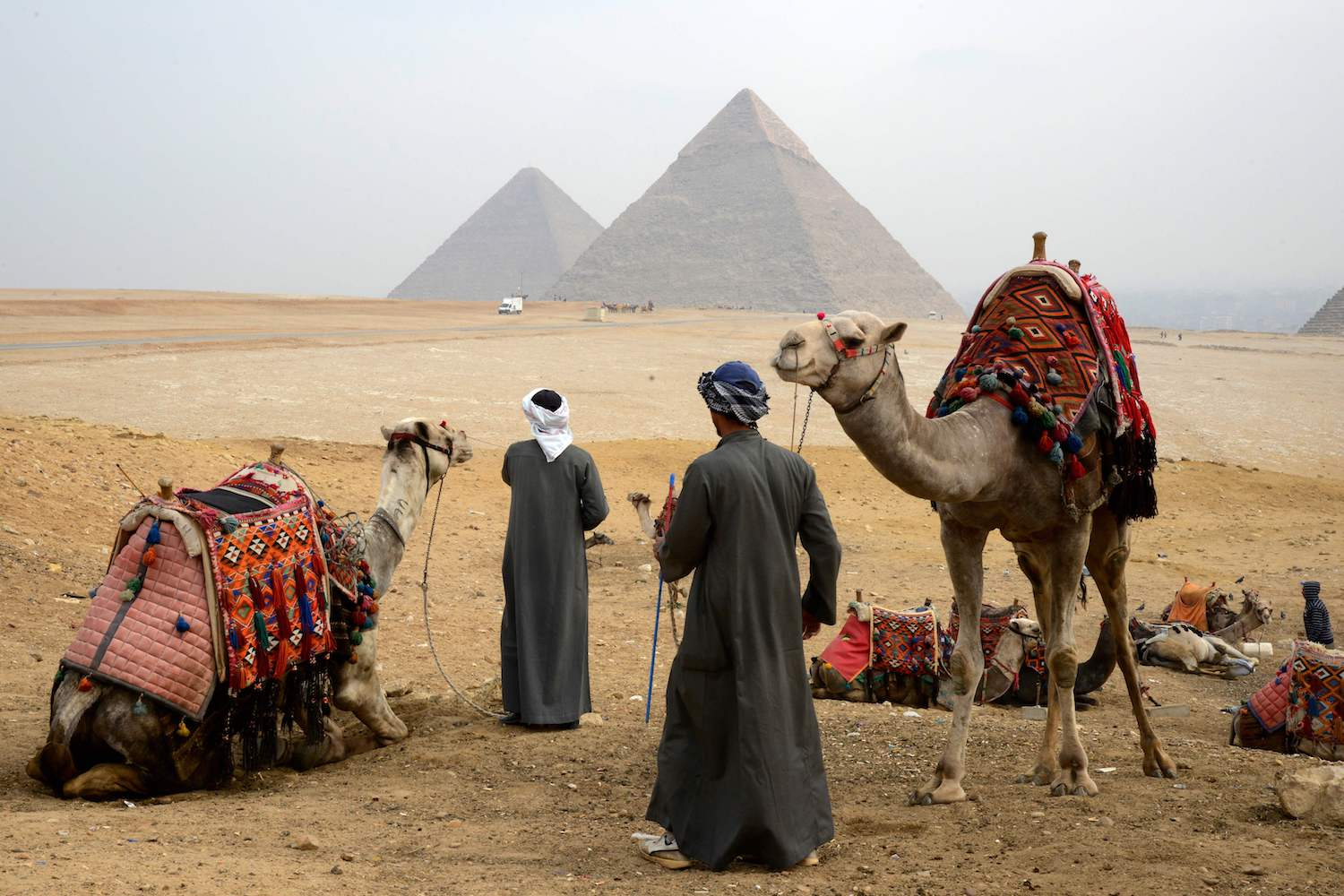 TOPSHOT - A picture taken on February 15, 2018 shows Egyptian tour guides preparing a caravan of camels for tourists as they sit across the Giza plateau from (R to L) the Great Pyramid of Khufu (Cheops), the Pyramid of Khafre (Chephren), and the Pyramid of Menkaure, on the southwestern outskirts of the capital Cairo. / AFP PHOTO / MARIO GOLDMAN        (Photo credit should read MARIO GOLDMAN/AFP/Getty Images)