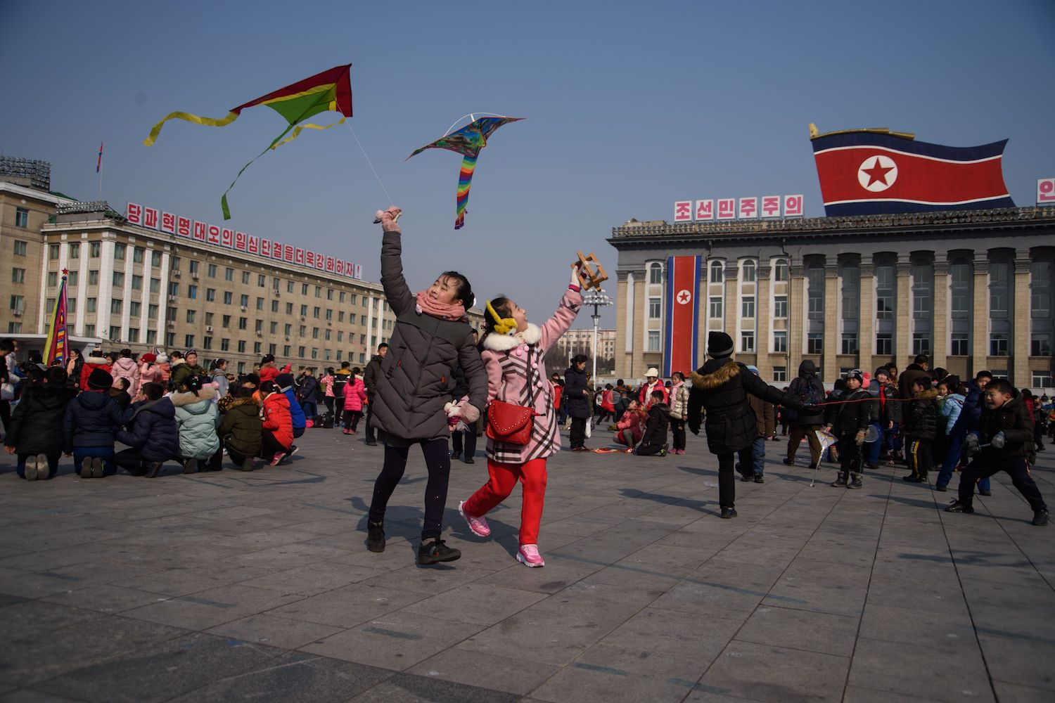 TOPSHOT - Children fly kites during Lunar New Year festivities on Kim Il Sung square in Pyongyang on February 16, 2018. / AFP PHOTO / KIM Won-Jin        (Photo credit should read KIM WON-JIN/AFP/Getty Images)