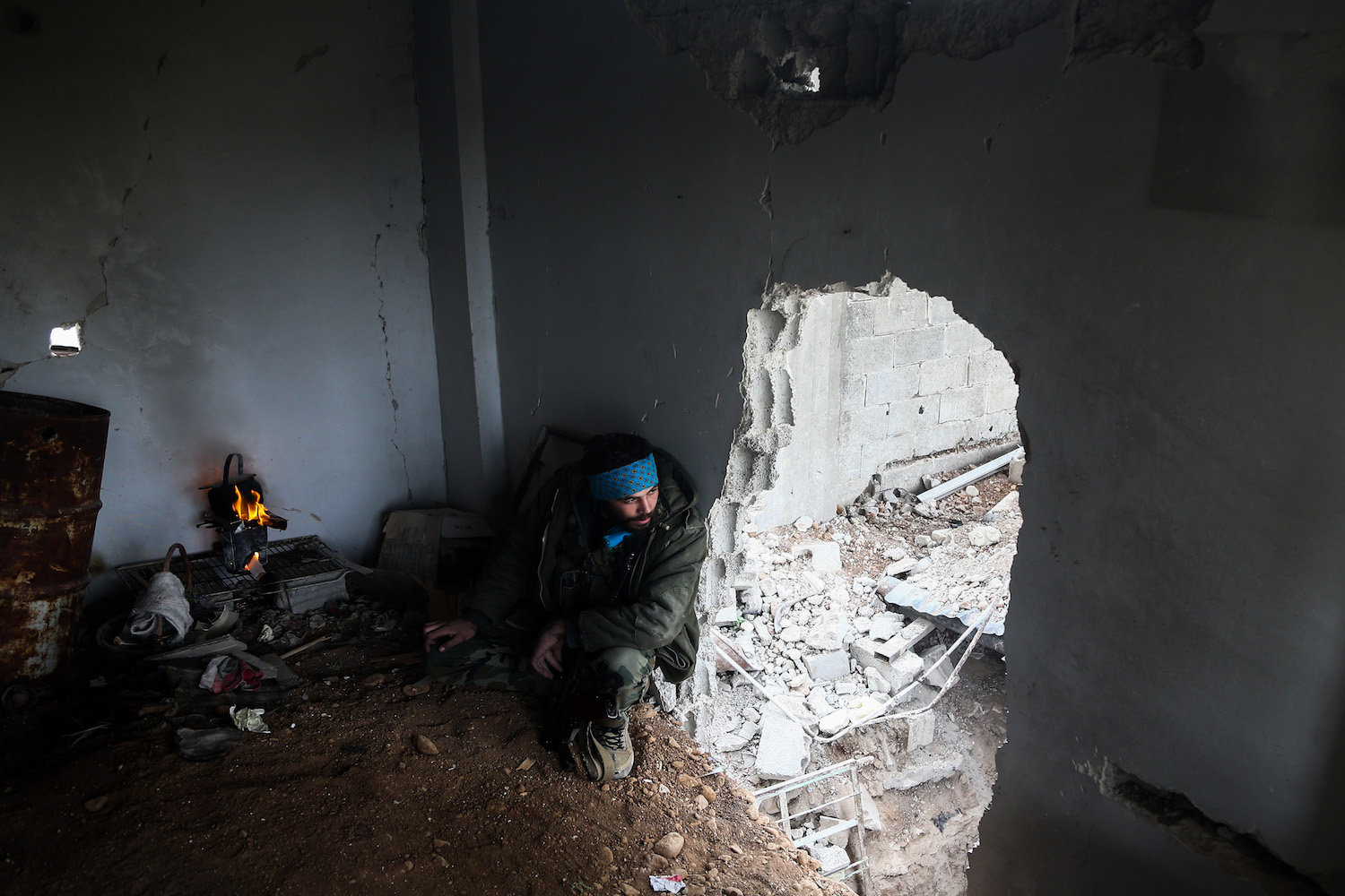 TOPSHOT - A Syrian opposition fighter from Failaq al-Rahman brigade sits by a fire next to a hole in a wall in a damaged building on the frontline in the rebel-held enclave of Arbin in the Eastern Ghouta near Damascus on February 15, 2018. / AFP PHOTO / ABDULMONAM EASSA        (Photo credit should read ABDULMONAM EASSA/AFP/Getty Images)