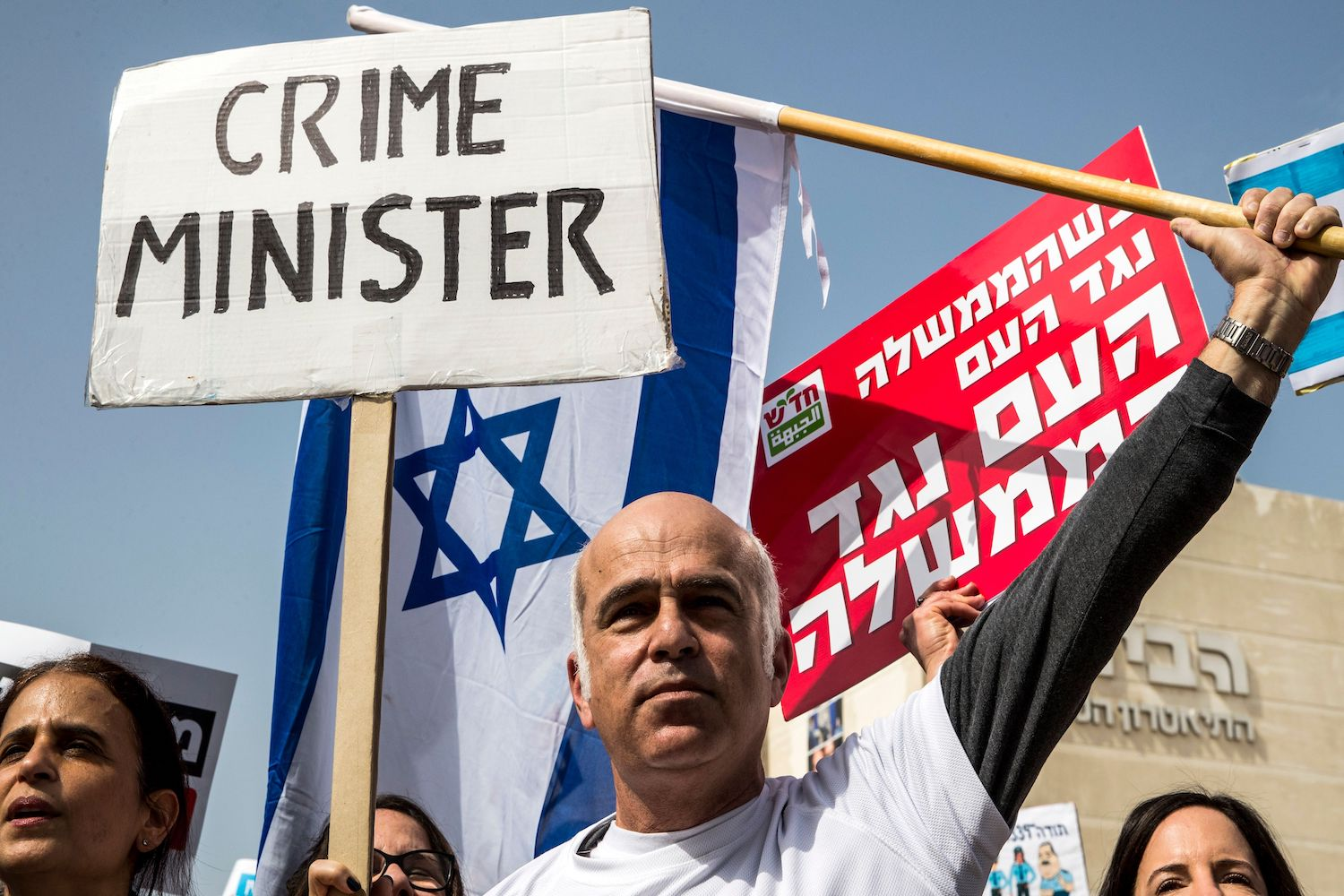 TOPSHOT - Israeli protesters raise signs as they demonstrate against Prime Minister Benjamin Netanyahu in the wake of police recommendations to indict corruption, in the coastal city of Tel Aviv on February 16, 2018. / AFP PHOTO / JACK GUEZ        (Photo credit should read JACK GUEZ/AFP/Getty Images)