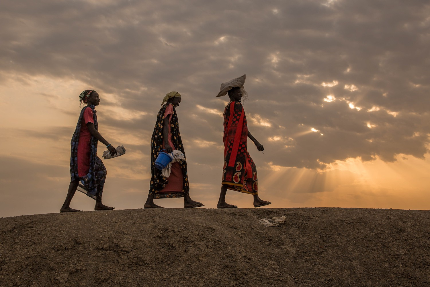TOPSHOT - Internally displaced women walk to a food distribution in the early morning at the Protection of Civilian site (PoC) in Bentiu, South Sudan, on February 13, 2018. Bentiu's Protection of Civilian site was established in January 2014, when 7,000 civilians entered the UNMISS base to seek protection, shortly after the start of the South Sudanese civil war. The camp hosts over 20,000 households and at least 114,250 individuals by IOM. the numbers keep growing every day, as fighting brings more people seeking safety.  / AFP PHOTO / Stefanie GLINSKI        (Photo credit should read STEFANIE GLINSKI/AFP/Getty Images)