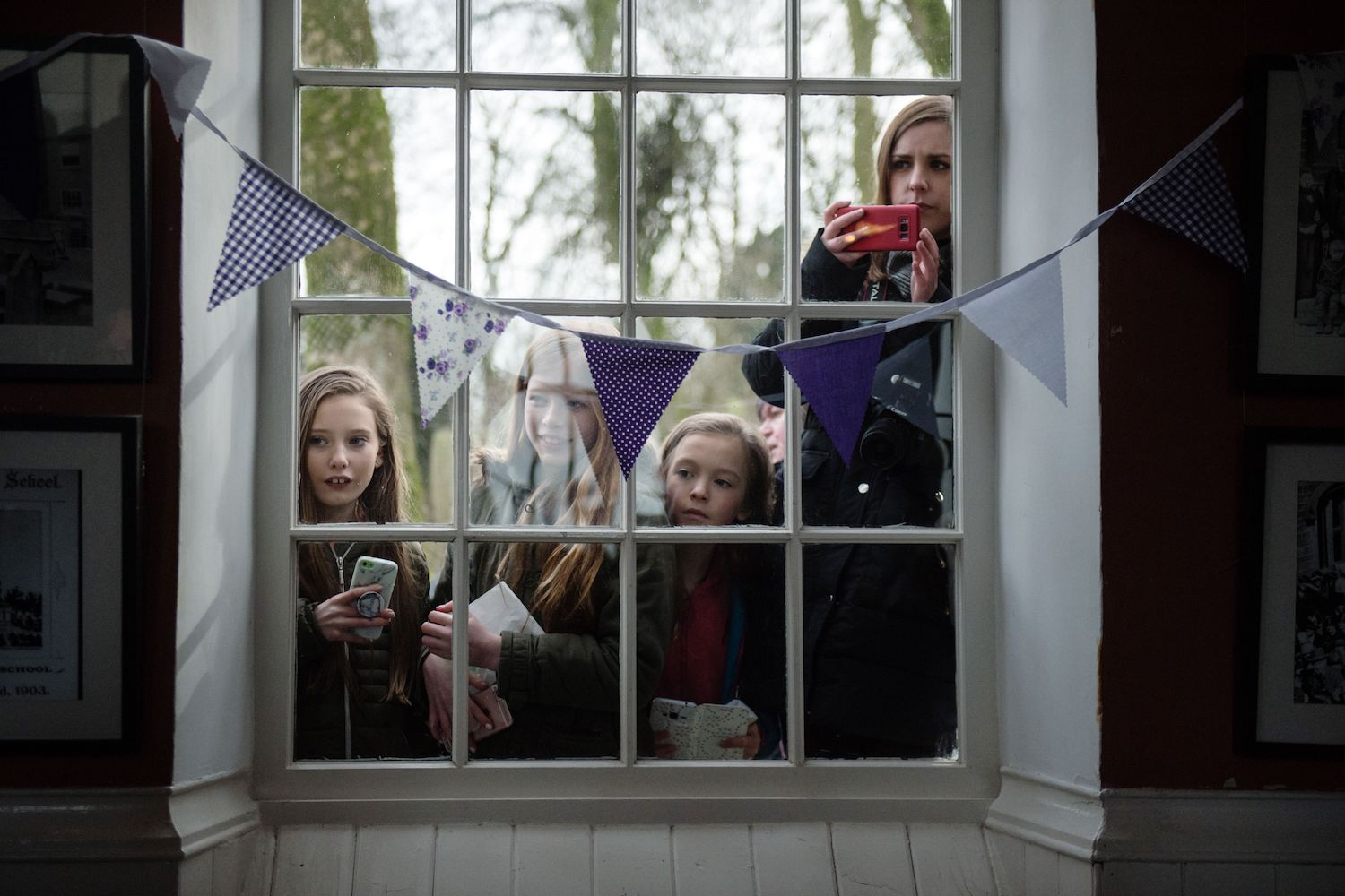 TOPSHOT - Members of the public watch as Britain's Camilla, Duchess of Cornwall speaks to school children after a visit to mark the bicentenary of the birth of Emily Bronte, to The Bronte Parsonage Museum, the former home of the Bronte family, in Haworth, northern England on February 16, 2018,   / AFP PHOTO / POOL / OLI SCARFF        (Photo credit should read OLI SCARFF/AFP/Getty Images)