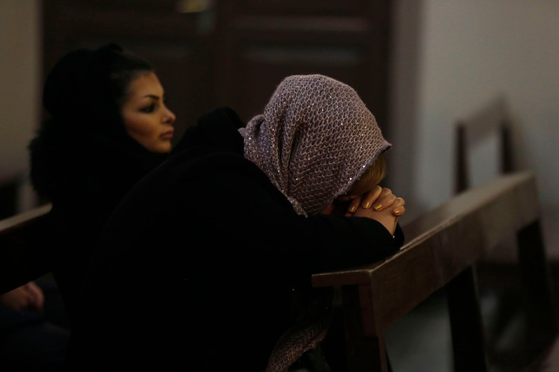 An Iranian woman prays as she attends Christmas Eve mass at the St Joseph Armenian Catholic church in Tehran on Dec. 24, 2016.        (Atta Kenare/AFP/Getty Images)