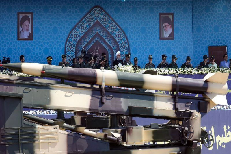 An Iranian medium range missile passes by Iranian President Hassan Rouhani (center) during a military parade on September 22, 2017 in Tehran.