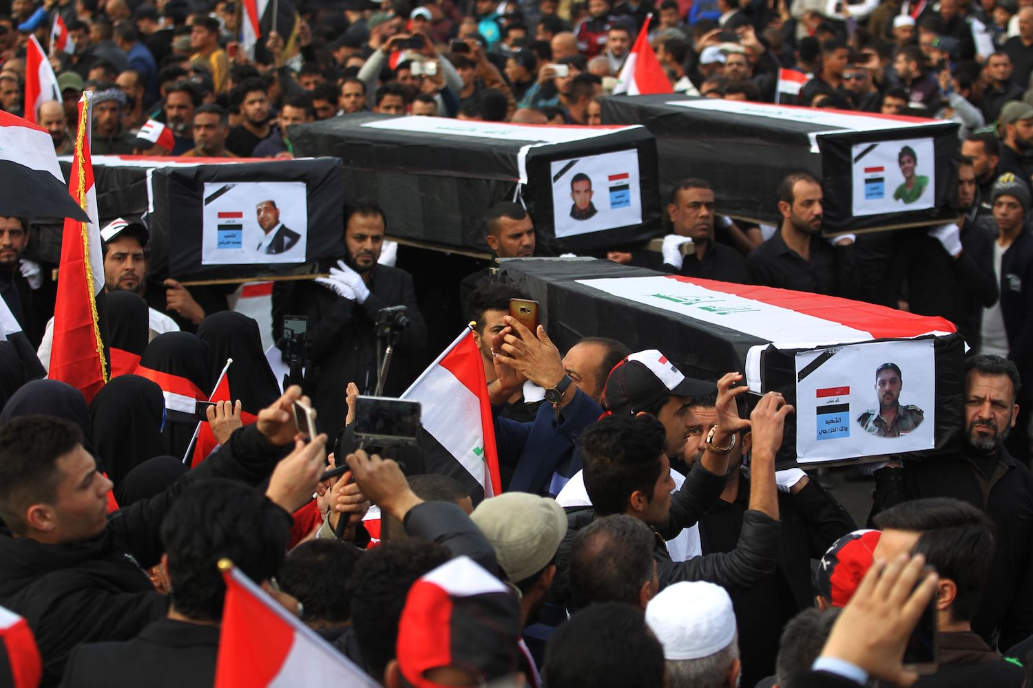 Iraqis carry mock coffins for those who were killed during a protest for electoral reform on February 11, 2017, as they march during a protest in Baghdad's Tahrir Square, on February 9, 2018. A year ago thousands of Sadr supporters and other Iraqis staged a demonstration demanding the country's election commissioners be replaced and the electoral law overhauled. The protest turned violent when some demonstrators tried to force their way through a security cordon to head to the seat of the electoral commission in the heavily fortified Green Zone. / AFP PHOTO / AHMAD AL-RUBAYE        (Photo credit should read AHMAD AL-RUBAYE/AFP/Getty Images)