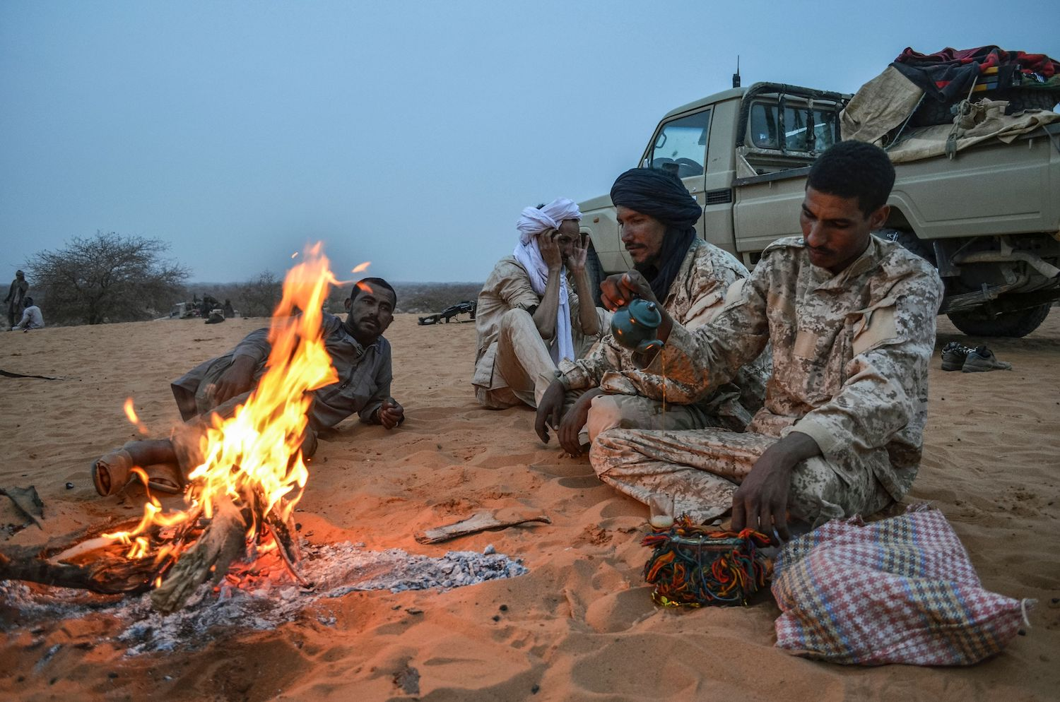 Militants of The Movement for the Salvation of Azawad sit as they brew tea at a waypoint while patrolling along the Mali-Niger border in the Menaka region of Mali during an anti-jihadist patrol on February 4, 2018. / AFP PHOTO / Souleymane AG ANARA        (Photo credit should read SOULEYMANE AG ANARA/AFP/Getty Images)