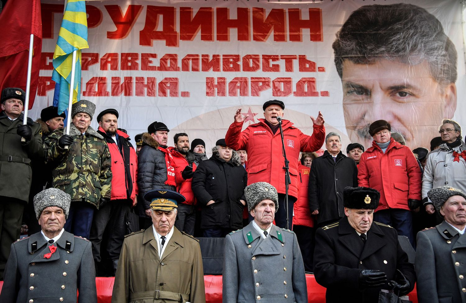 Veteran leader of Russian Communist party Gennady Zyuganov (center) speaks in front of a banner depicting Communist presidential candidate Pavel Grudinin during a rally in downtown Moscow on Feb. 23, marking the Defender of the Fatherland's Day, former Day of the Soviet Army. The Communist Party chose a new face for the March 18, 2018 polls, opting for businessman Pavel Grudinin rather than veteran leader Gennady Zyuganov. / AFP PHOTO / Alexander NEMENOV        (Photo credit should read ALEXANDER NEMENOV/AFP/Getty Images)