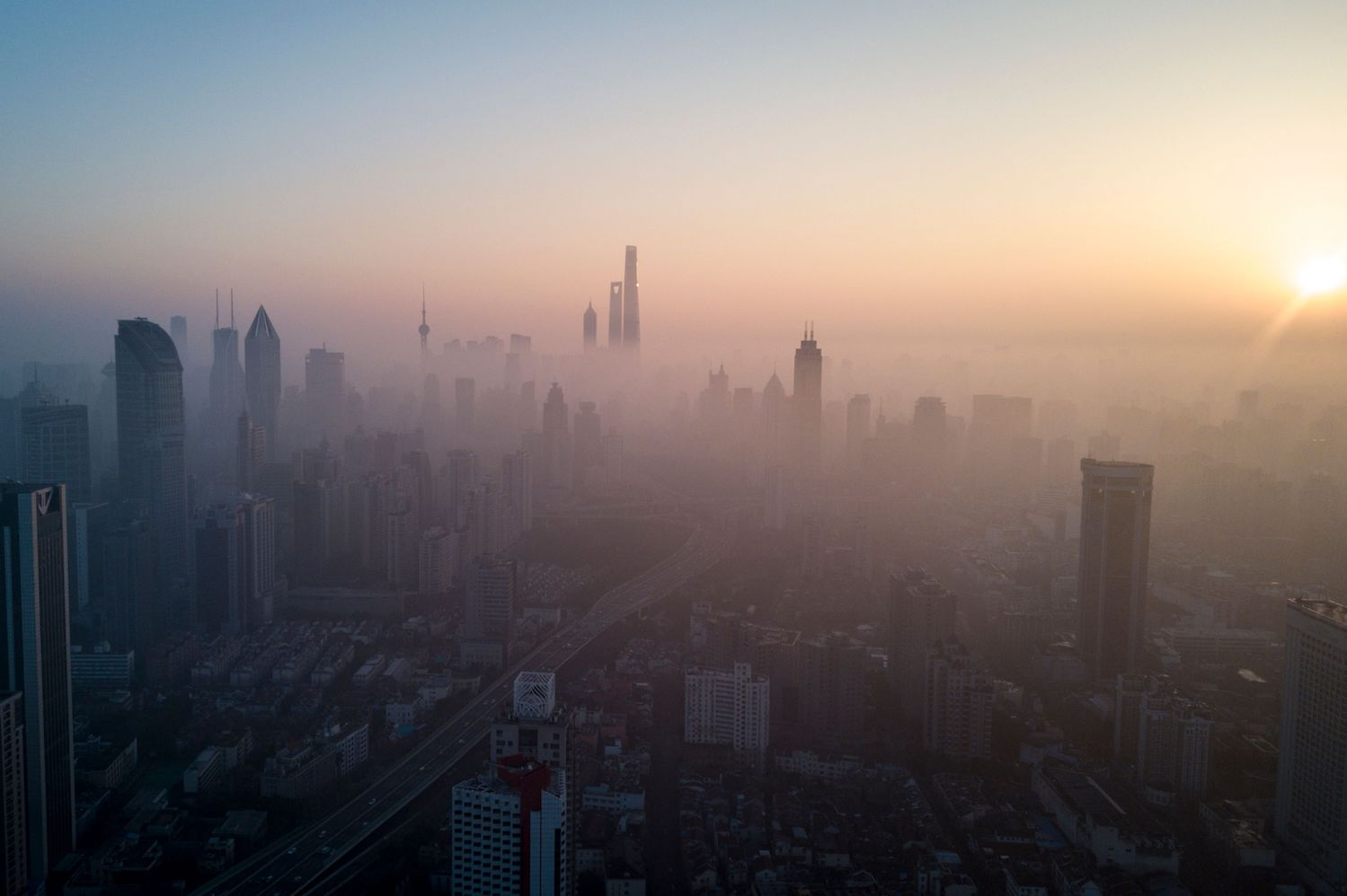 This overhead photo shows the sun rising above the skyline of Shanghai on a polluted day on February 23, 2018. / AFP PHOTO / Johannes EISELE        (Photo credit should read JOHANNES EISELE/AFP/Getty Images)