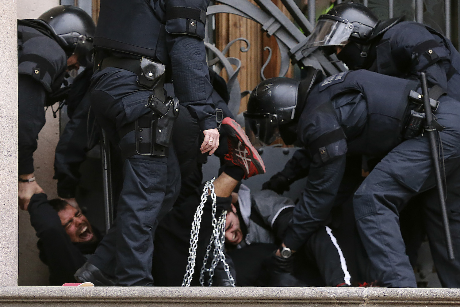 Catalan regional police officers (Mossos d'Esquadra) remove two chained men during a protest called by the 'Commitees in defence of the Republic' to block the TSJC (Superior Court of Justice of Catalonia) in Barcelona on February 23, 2017. / AFP PHOTO / PAU BARRENA        (Photo credit should read PAU BARRENA/AFP/Getty Images)