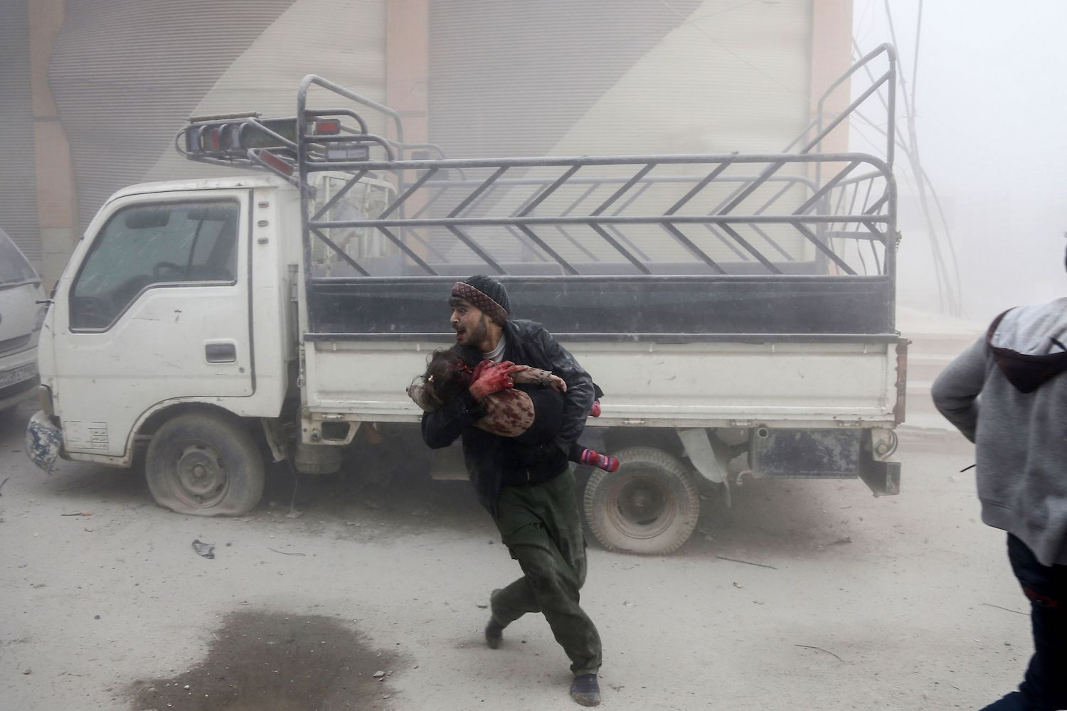 A man carries a child as he flees from reported Syrian air force strikes that hit the rebel-held town of Saqba, in the besieged Eastern Ghouta region on the outskirts of the capital Damascus, on February 6, 2018. Fresh regime strikes on a besieged rebel-held enclave near Damascus killed more than 60 civilians on February 6, despite mounting Western pressure on Syrian President Bashar al-Assad. / AFP PHOTO / ABDULMONAM EASSA        (Photo credit should read ABDULMONAM EASSA/AFP/Getty Images)
