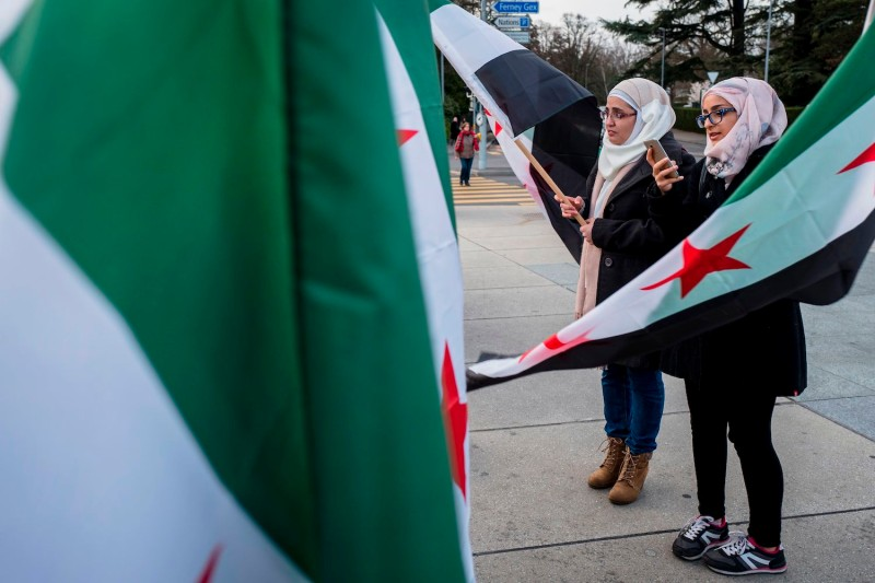 "Activits hold Syrian flags as they take part in a protest marking the 6th years since the beginning of the syrian uprising organized by Syrian organization ""Femmes pour la Démocratie"" (Womens for Democracy) during Syria peace talks in Geneva on March 23, 2017. (Fabrice Coffrini/AFP/Getty Images)"