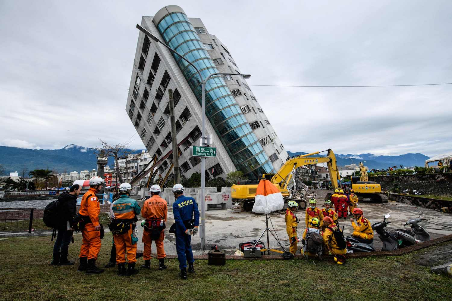 Japanese (left) and Taiwanese rescue workers (right) look at the Yun Tsui building (center), which is leaning at a precarious angle, in the Taiwanese city of Hualien on Feb. 9, after the city was hit by a 6.4-magnitude quake late on Feb. 6. (Photo credit should read ANTHONY WALLACE/AFP/Getty Images)