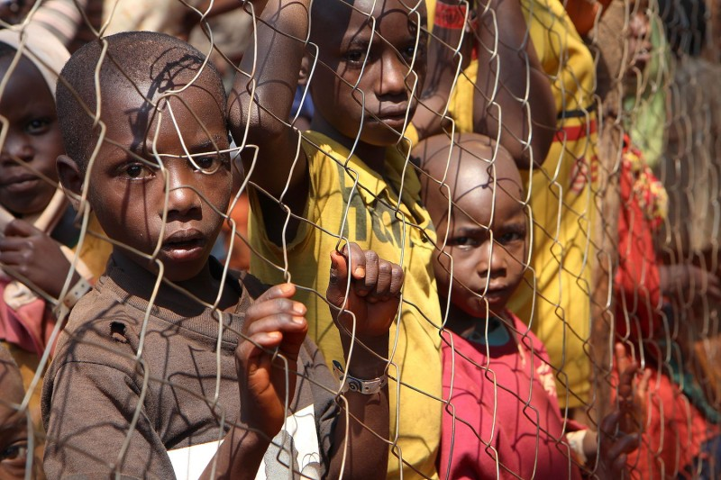 Burundian children, who fled their country, stand behind a fence as they wait to be registered as refugees at Nyarugusu camp, in north west of Tanzania, on June 11, 2015. (Stephanie Aglietti/AFP/Getty Images)