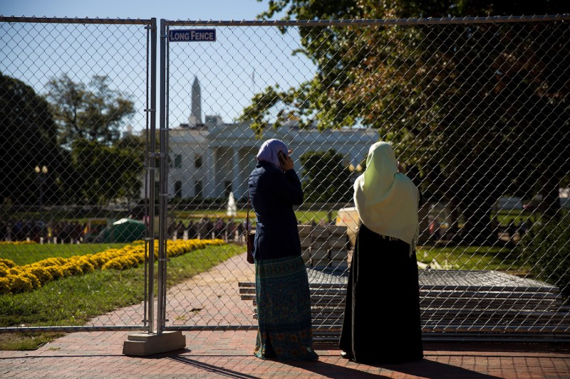 Two Muslim women stand near a fence across the street from the White House before the start of a protest against the Trump administration's proposed travel ban, in Washington on Oct. 18, 2017. (Drew Angerer/Getty Images)