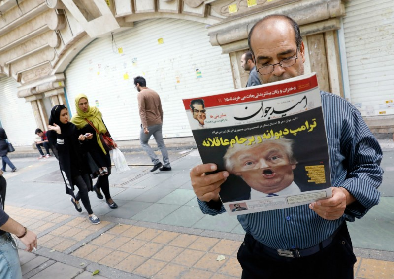 An Iranian man reads a copy of the daily newspaper 'Omid Javan' bearing a picture of US President Donald Trump on Oct. 14, 2017, in front of a kiosk in Tehran. (STR/AFP/Getty Images)