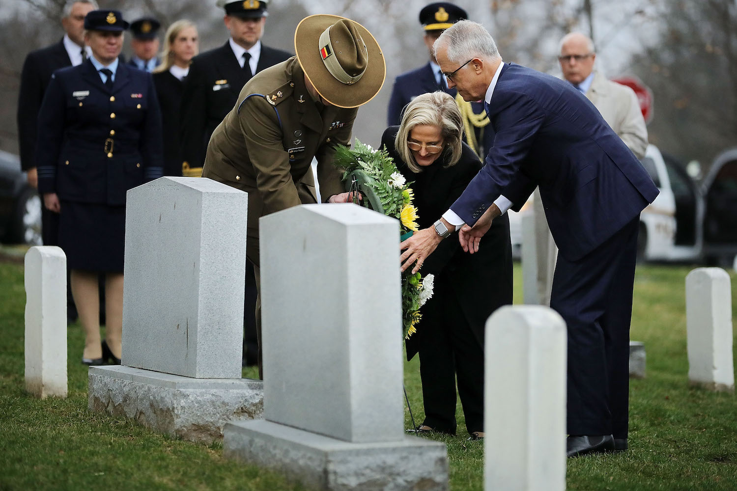 Australian Prime Minister Malcolm Turnbull (right) and his wife Lucy Turnbull (center) are assisted by Australian Army Lt. Col. Adrian Trappett as they lay a wreath the grave of Royal Australian Air Force Pilot Francis D. Milne at Arlington National Cemetery in Arlington, Virginia on Feb. 22. (Chip Somodevilla/Getty Images)