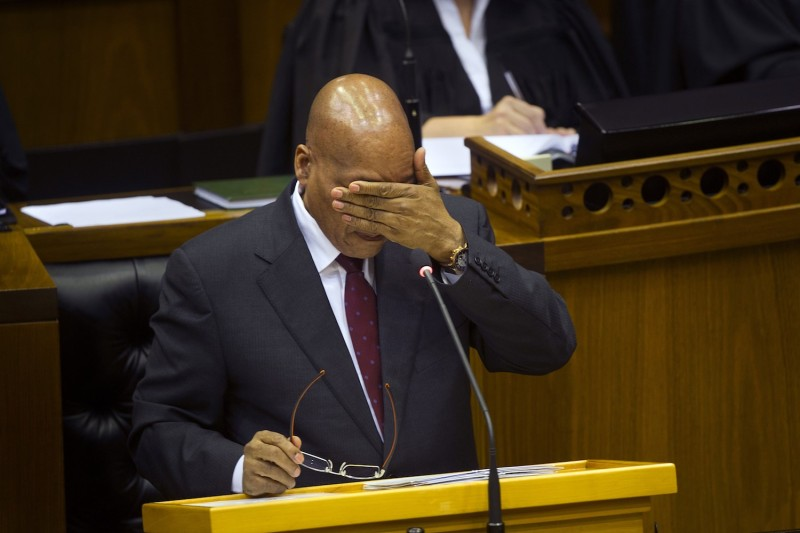 South African President Jacob Zuma wipes his face with his hand as he answers hostile questions at the South African parliament in Cape Town on August 6, 2015.