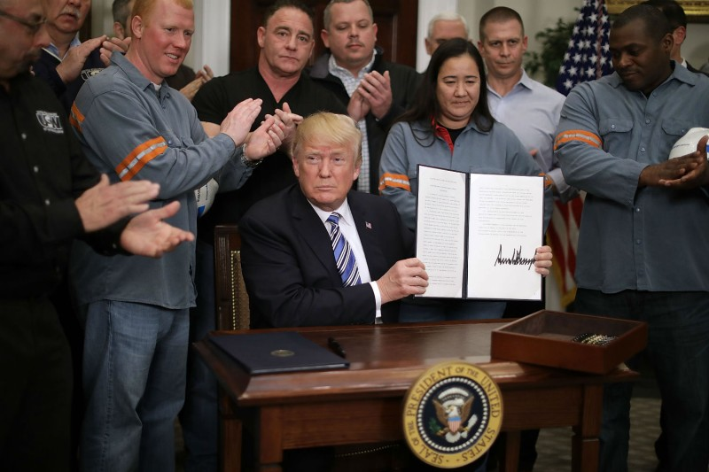President Donald Trump, surrounded by steel and aluminum workers, proclaims new tariffs that many fear will spark a trade war, Mar. 8, 2018. (Chip Somodevilla/Getty Images)