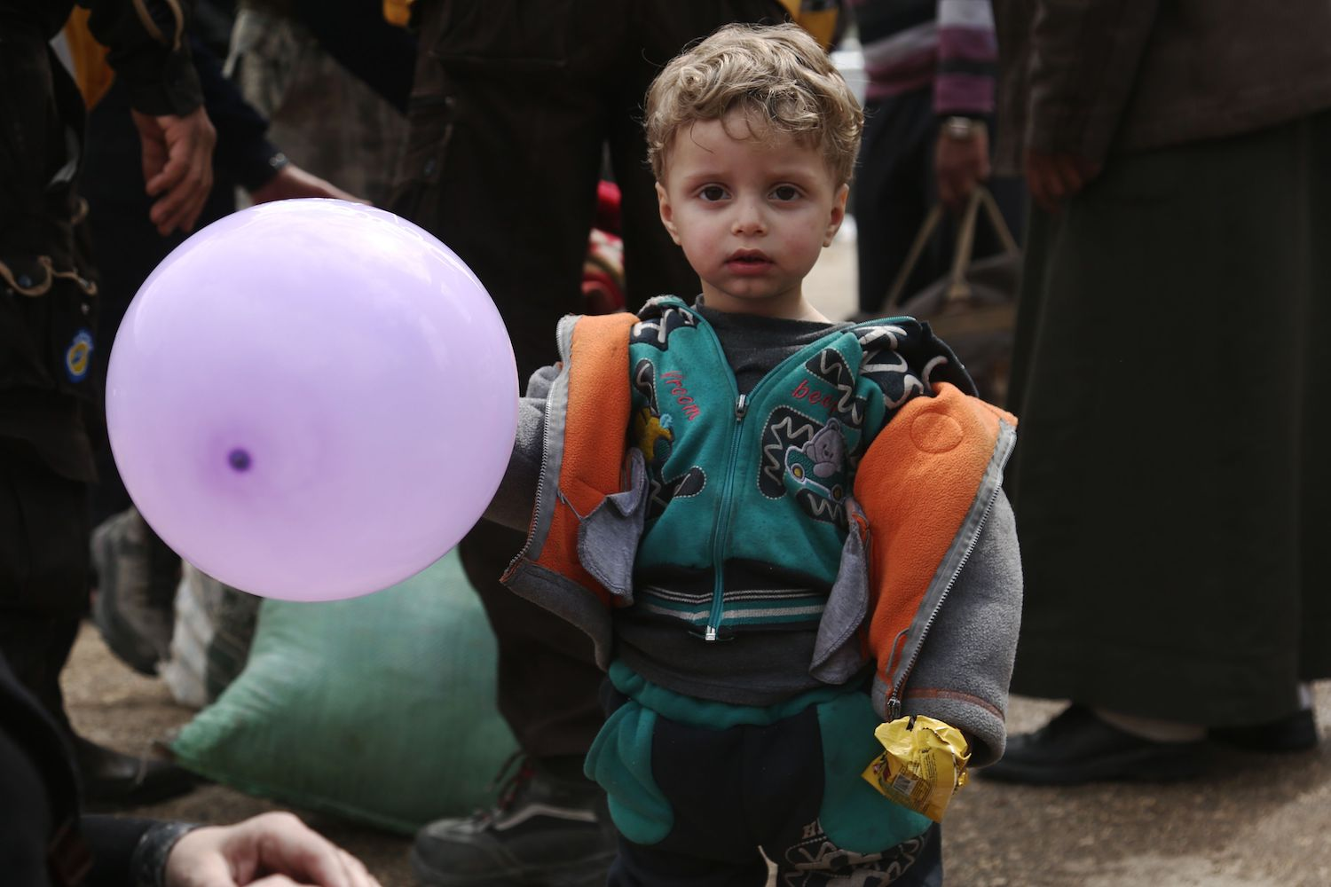 A Syrian boy plays with a balloon upon arriving with a convoy carrying civilians and rebel fighters in the village of Qalaat al-Madiq, north of Hama on March 25, after being evacuated from Eastern Ghouta following a deal with the regime. The deal is expected to see some 7,000 people bussed from Arbin and Zamalka towns and the district of Jobar to a rebel-dominated part of northern Syria. / AFP PHOTO / Zein Al RIFAI        (Photo credit should read ZEIN AL RIFAI/AFP/Getty Images)