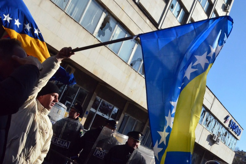 A demonstrator waves a Bosnian flag as police stand guard while protesters gather in front of a local government building in Tuzla in February 2014. (Elvis Barukcic/AFP/Getty Images)