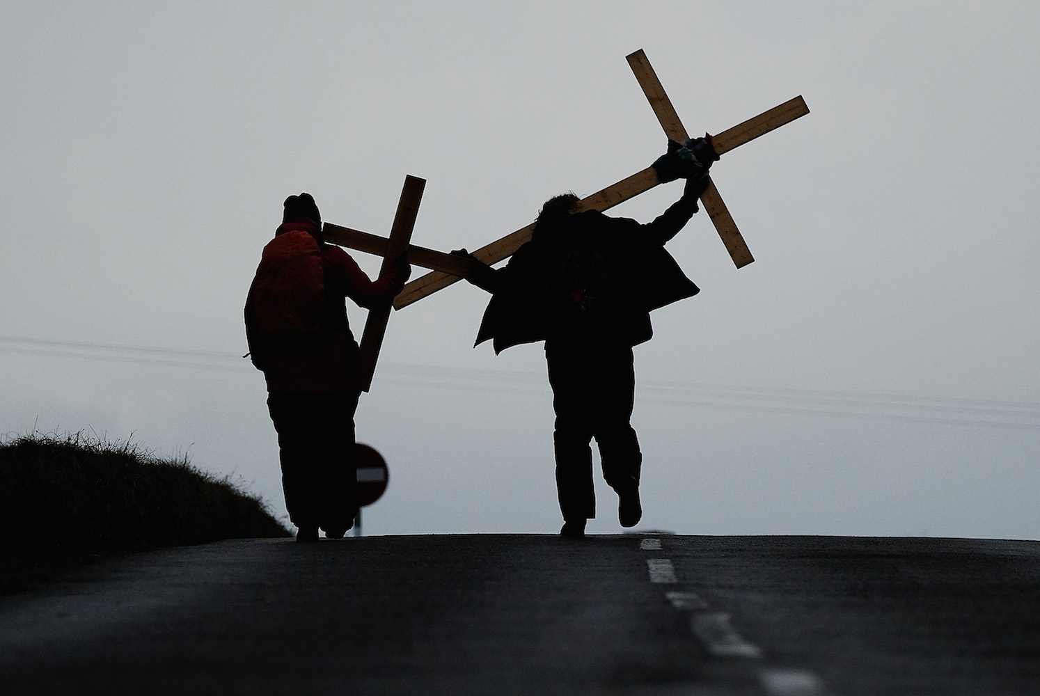 Pilgrims celebrate Easter by crossing over the tidal causeway carrying wooden crosses on the final leg of their annual pilgrimage to the Holy Island of Lindisfarne on March 30, 2018 in Berwick-upon-Tweed, England. Around 100 people of all ages and backgrounds celebrated Easter by crossing at low tide during the pilgrimage which ends on the island. The event is organised by Northern Cross and sees pilgrims walking between 70 to 120 miles in the week leading up to the Good Friday crossing. (Photo by Ian Forsyth/Getty Images)