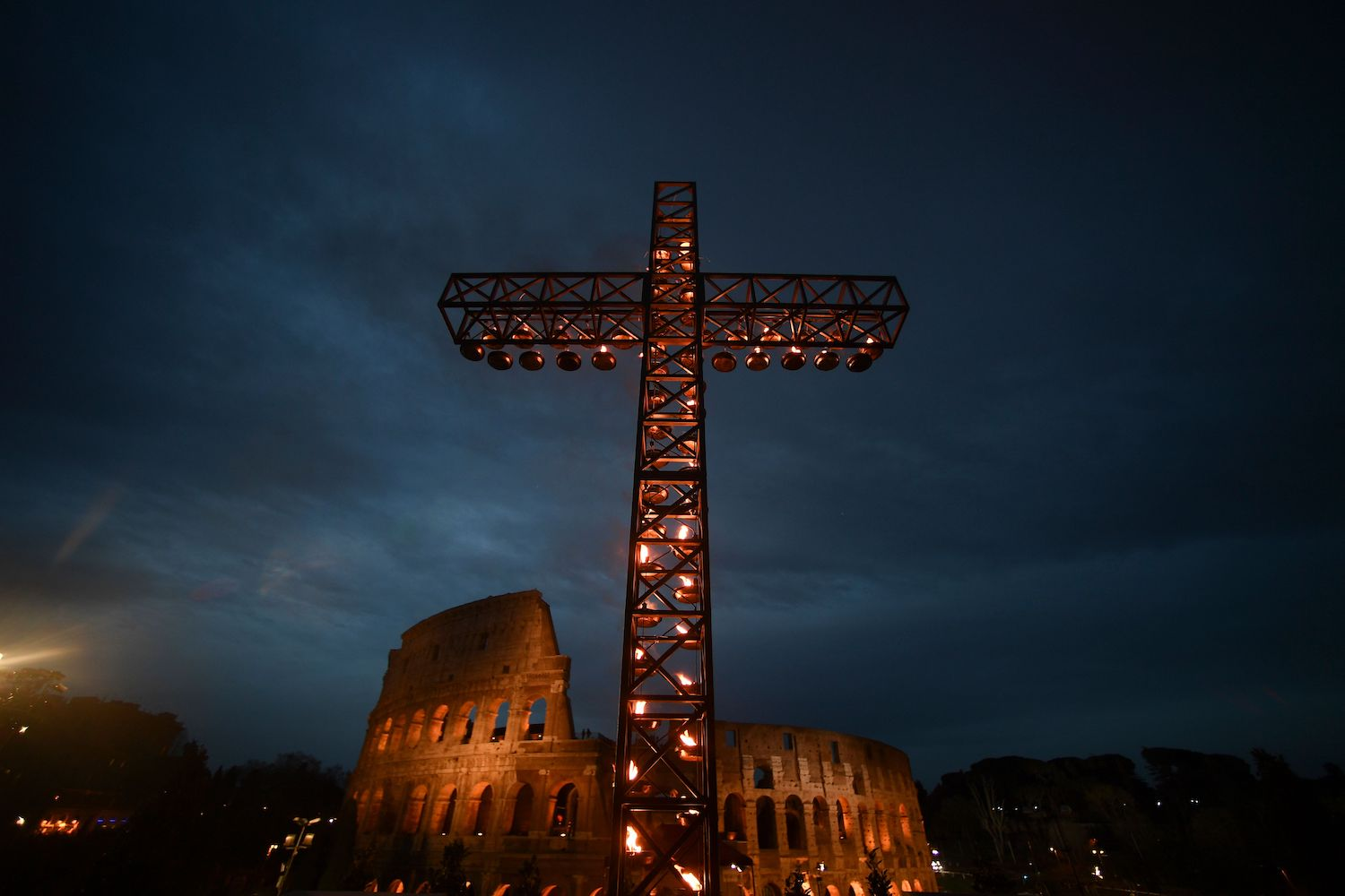 A cross is lighted before the arrival of Pope Francis for the Via Crucis (Way of the Cross) torchlight procession at the ancient Colosseum on Good Friday, on March 30, 2018 in Rome. Christians around the world are marking the Holy Week, commemorating the crucifixion of Jesus Christ, leading up to his resurrection on Easter. / AFP PHOTO / Filippo MONTEFORTE        (Photo credit should read FILIPPO MONTEFORTE/AFP/Getty Images)