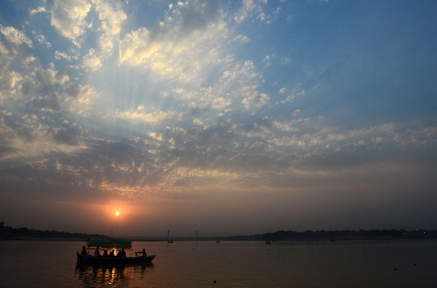 Indian people take an evening boat ride during sunset at the Sangam, the confluence of the Yamuna and Ganges river in Allahabad on March 23, 2018. / AFP PHOTO / SANJAY KANOJIA        (Photo credit should read SANJAY KANOJIA/AFP/Getty Images)