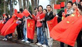 Chinese consular staff wave national flags in front of a demonstration by supporters of the Falungong spiritual movement outside the venue where China's Vice President Xi Jinping was opening Australia's first Chinese Medicine Confucius Institute, at the RMIT University in Melbourne on June 20, 2010. (William West/AFP/Getty Images)