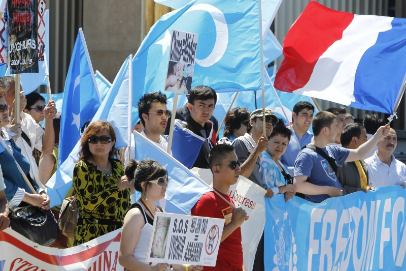 People hold flags and placards during a demonstration of France's exiled Uyghur community on July 4, 2010 on Place du Trocadero in Paris to commemorate the 1st anniversary of the events of July 5, 2009 in Urumqi in China, when Uyghur demonstrations were brutally suppressed by Chinese security forces. (Francois Guillot/AFP/Getty Images)
