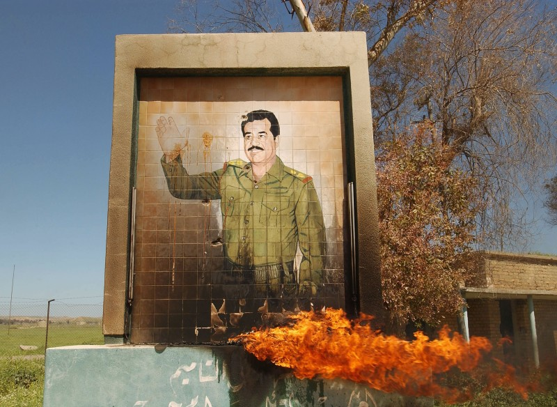 A burning mural of Saddam Hussein in Kirkuk on April 11, 2003. (Patrick Barth/Getty Images)
